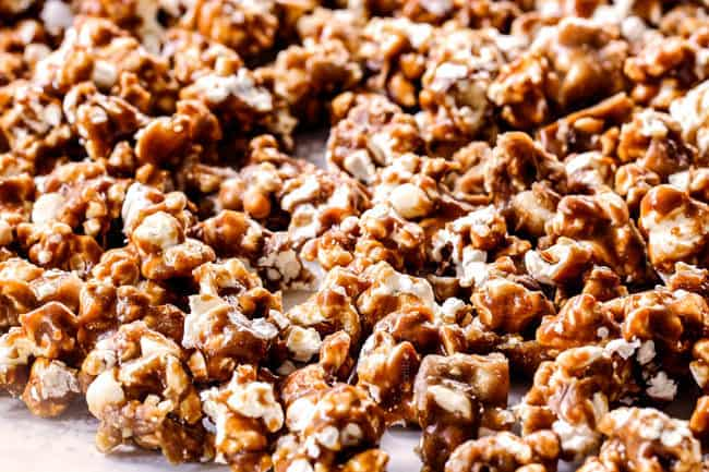 showing how to make caramel popcorn by spreading baked popcorn out on parchment paper