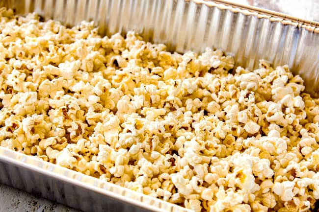 showing how to make caramel popcorn by adding popped popcorn to a large pan