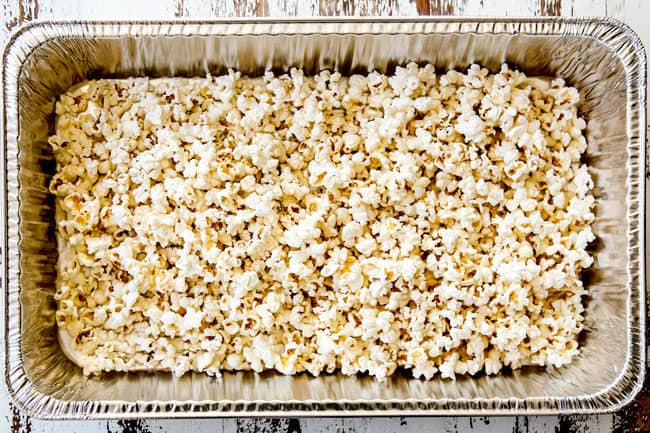 showing how to make caramel popcorn by adding popcorn to a large pan