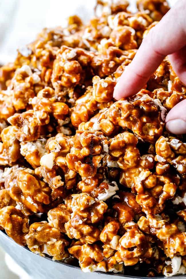 two fingers taking a piece of caramel popcorn from a large bowl