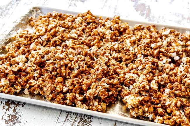 showing how to make caramel popcorn by spreading caramel covered popcorn out on a baking tray before going into the oven