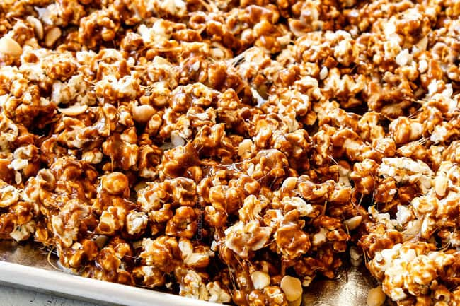 up close of showing how to make caramel popcorn by spreading caramel covered popcorn out onto a baking sheet