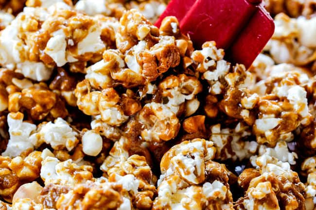 showing how to make caramel popcorn by stirring air popped popcorn with caramel