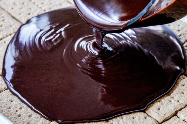 showing how to make easy Chocolate Eclair Cake by pouring chocolate ganache over graham crackers