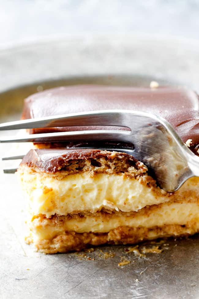 a fork taking a bite of side view of Chocolate Eclair Cake with chocolate frosting