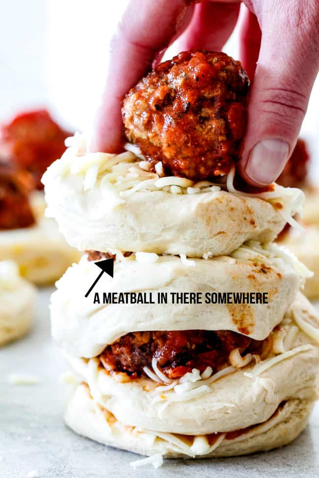 showing how to make pull apart bread by stacking biscuits together with cheese and meatballs