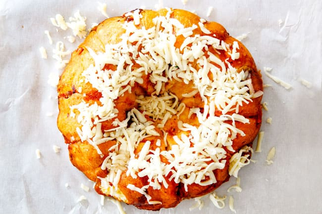 showing how to make pull apart bread by adding cheese to top of baked biscuits