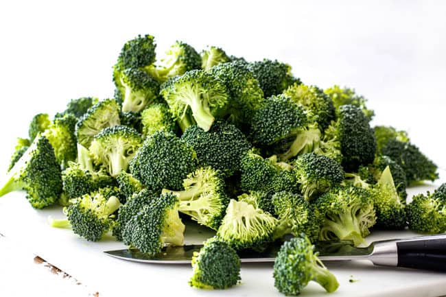 chopped broccoli florets on a white cutting board easy chicken divan recipe