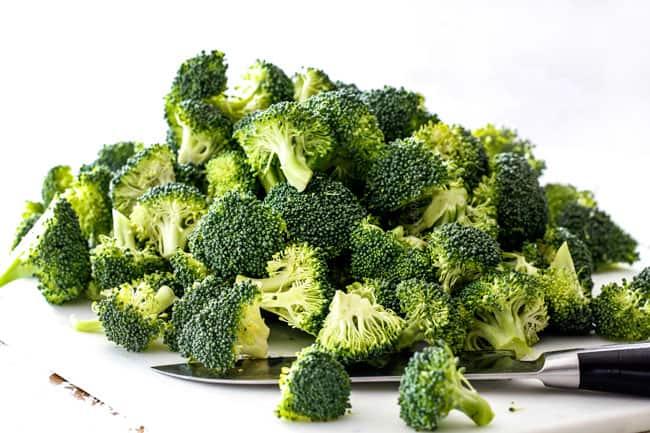 chopped broccoli florets on a white cutting board easy chicken divan recipe