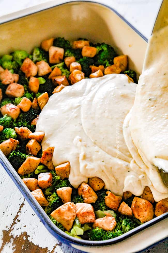 showing how to make chicken divan by pouring creamy sauce over chicken and broccoli