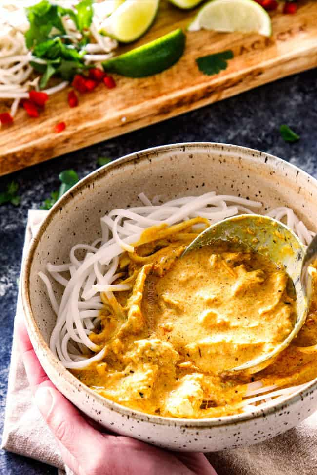 spooning best ever laksa recipe over rice noodles in a bowl