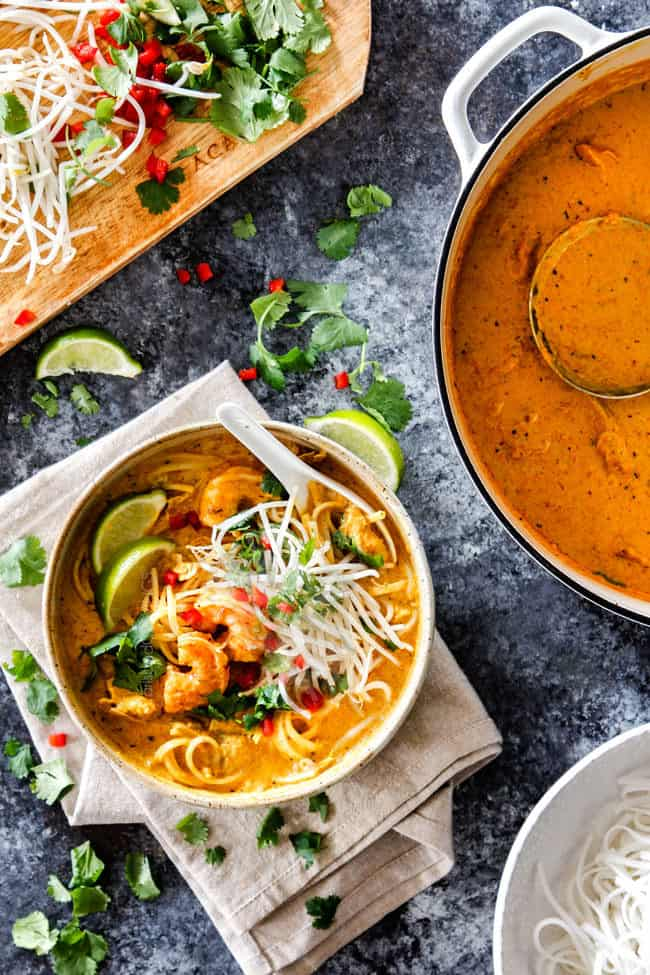 top view of a bowl of laksa soup with noodles, chicken and shrimp with a pot of laksa soup and a cutting board of bean sprouts, cilantro and peppers