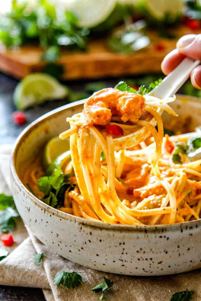a spoonful of laksa with chicken, shrimp and noodles and cilantro and bean sprouts