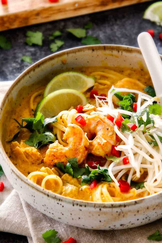side view of a bowl of laksa soup with bean sprouts, shrimp, chicken and cilantro