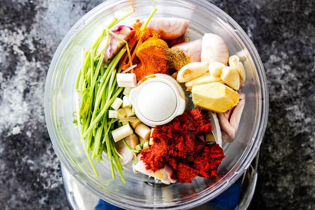 showing how to make Laksa paste for best ever laksaa recipe by adding ginger, lemongrass, shallots, garlic, turmeric, cumin, cilantro stems and red curry paste to food processor