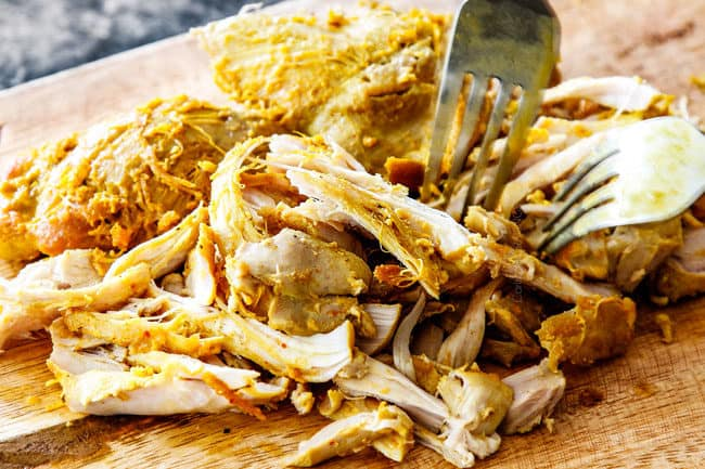 showing how o make laksa by shredding chicken on a wood cutting board
