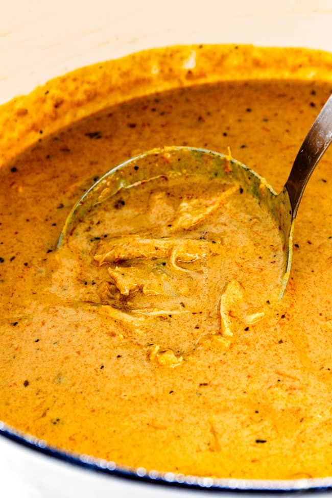 up close of creamy laksa with chicken in a white pot