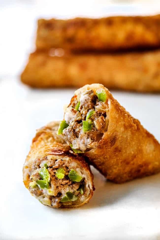 two Philly Cheesesteak egg roll halves stacked on a white marble board