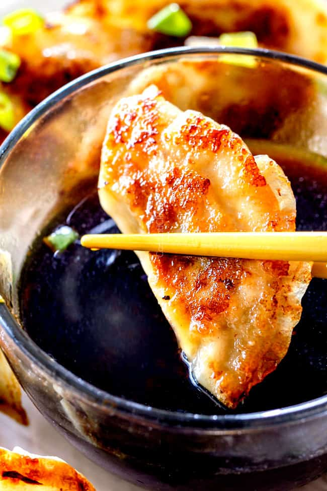 up close of two chopsticks holding a potsticker getting ready to dunk it in potsticker dipping sauce