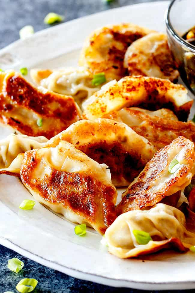 many homemade potstickers laying different directions on a platter