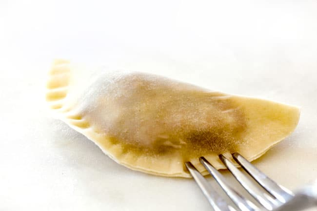 showing how to make potstickers by sealing the edges with the tongs of a fork