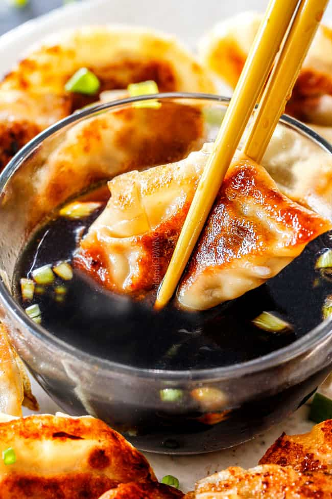 two chopsticks dunking a crispy potsticker in soy vinegar dipping sauce