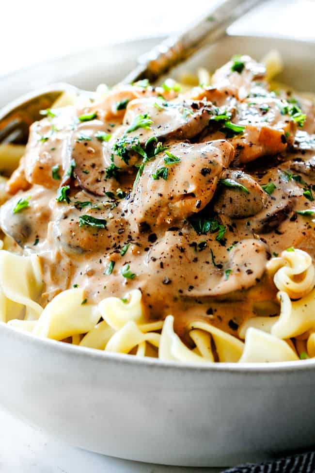 up close view of Chicken Stroganoff with tender chicken in a white bowl on top of egg noodles garnished with parsley