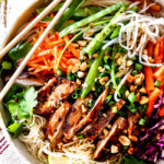 top up close view of Vietnamese noodle with rice noodles, lemongrass chicken, shredded carrots, julienned carrots, bean sprouts and snow peas