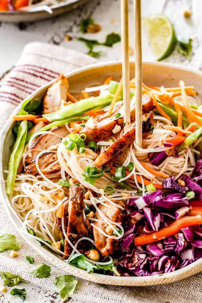 chopsticks picking up lemongrass chicken in Vietnamese Noodles