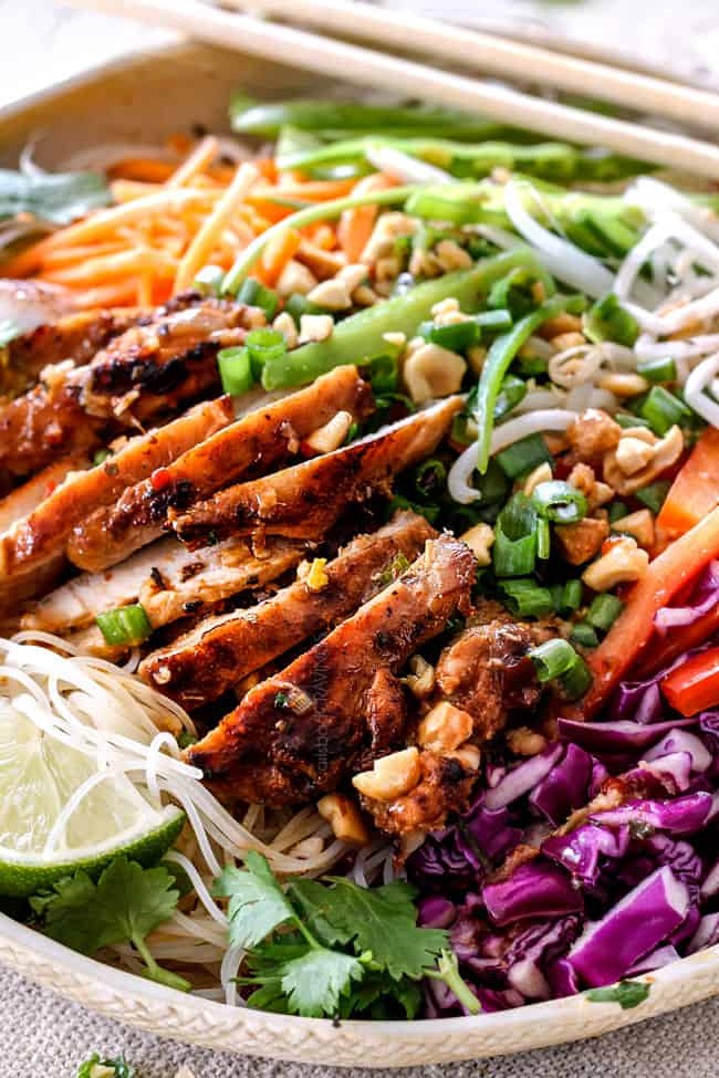 side view of Vietnamese noodle with rice noodles, lemongrass chicken, shredded carrots, julienned carrots, bean sprouts and snow peas