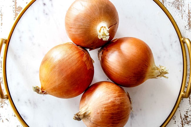 showing yellow onions on a white marble cutting board as the best onions for French Onion Soup