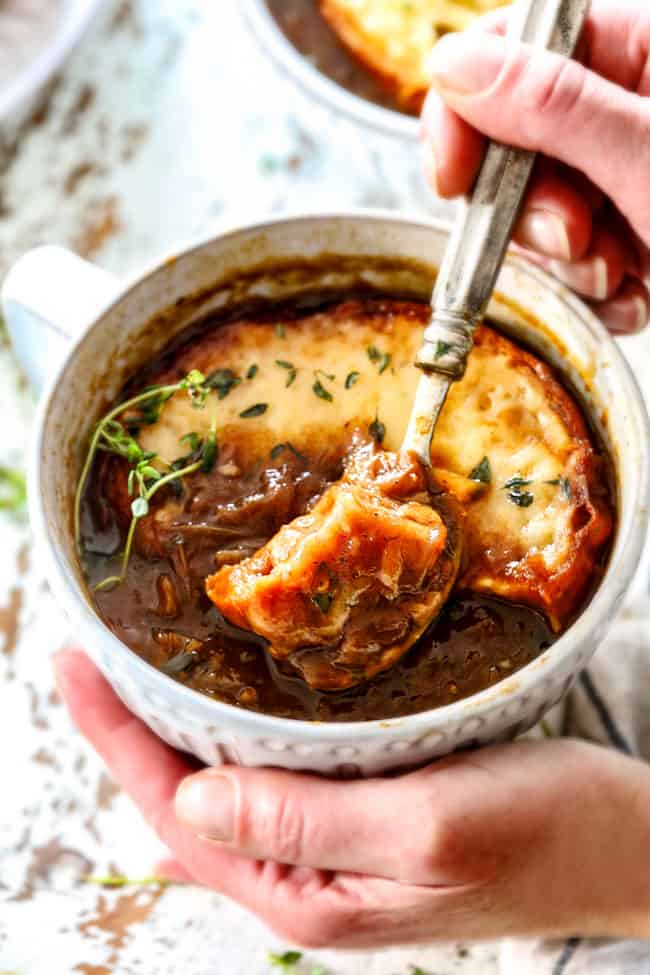two hands holding a bowl of classic French Onion Soup