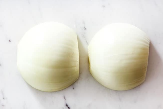 showing how to cut onions for French Onion Soup by slicing onions in half