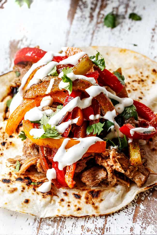 showing how to make pork fajitas by adding pork bell peppers and sour cream to a tortilla