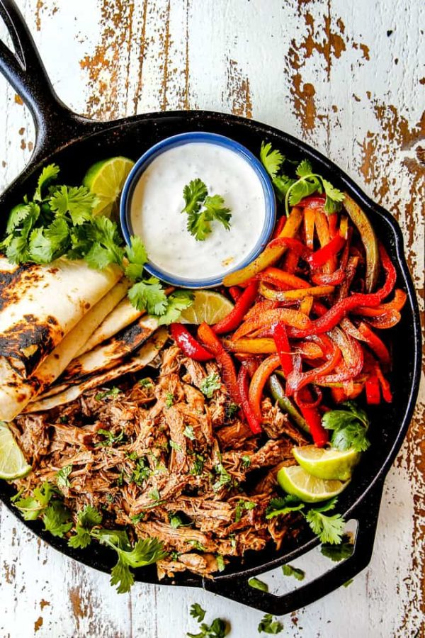 top view of pork fajitas in a skillet with salsa verde pork, bell peppers, onions, limes, cilantro and tortillas
