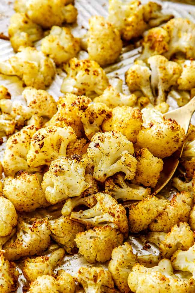 a spoonful of Parmesan roasted cauliflower on a baking sheet
