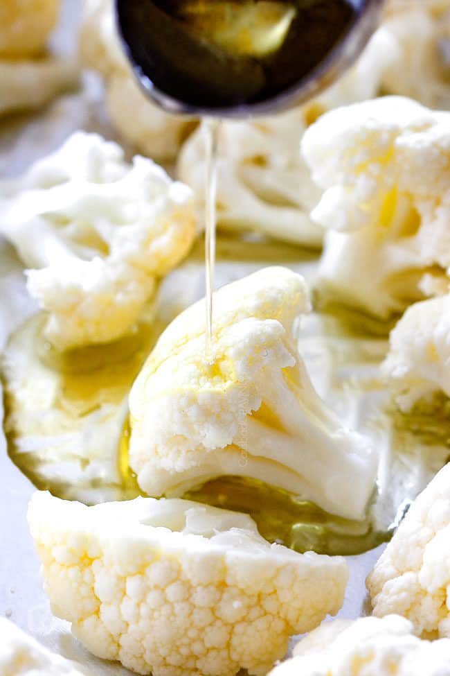 showing how to make roasted cauliflower by drizzling with olive oil