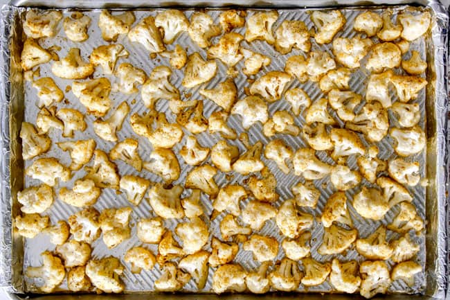 showing how to make roasted cauliflower by laying seasoned cauliflower in a single layer on a baking sheet