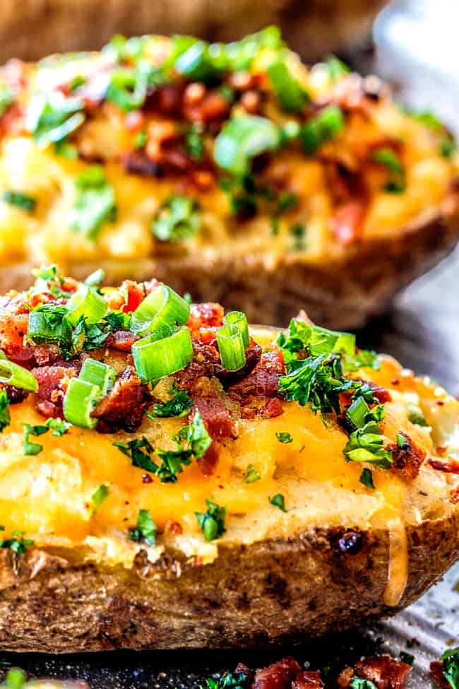 up close side shot of twice baked potatoes lined on a baking sheet