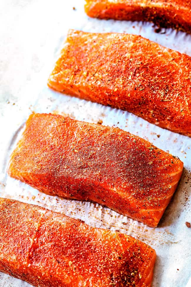 showing how to make Blackened Salmon by seasoning with blackened seasoning