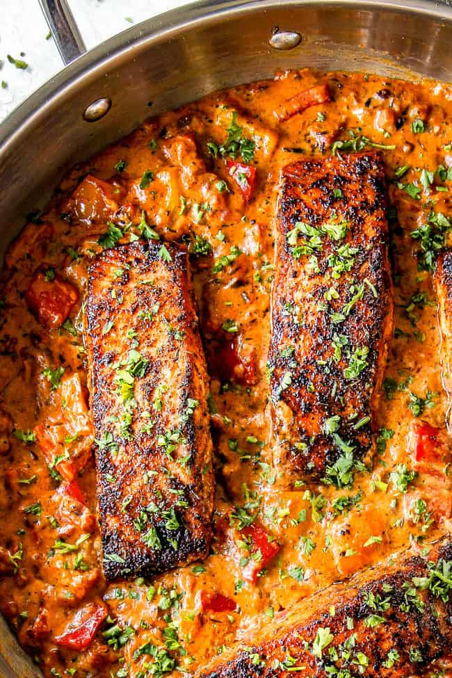 top vew of 2 blackened salmon fillets in a skillet with sauce