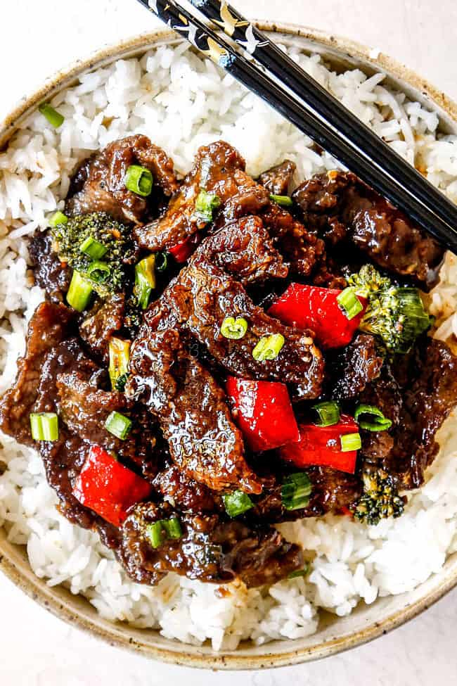 up close op view of authentic Mongolian Beef recipe in a bowl with black chopsticks
