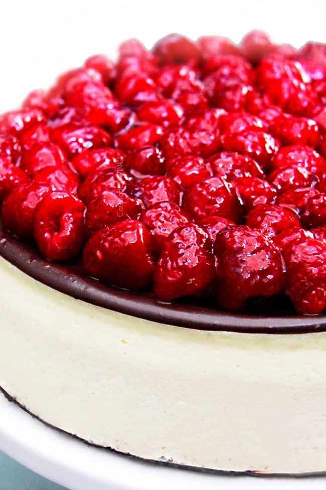 chocolate ganache cheesecake with a row of raspberries on top