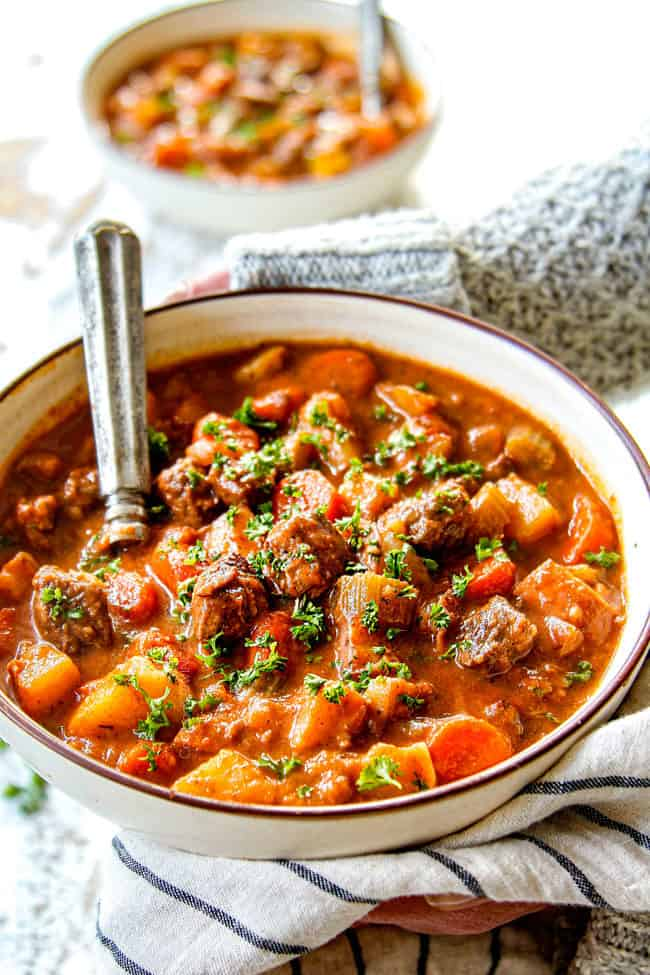 two hands showing how to serve beef stew by holding with two hands and garnishing with parsley