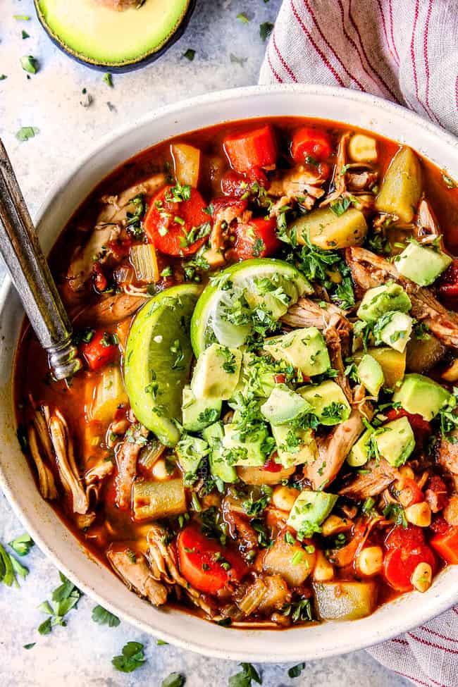 a bowl of authentic Caldo de pollo (Mexican Chicken Soup) toppd with avocadoes, cilantro and limes