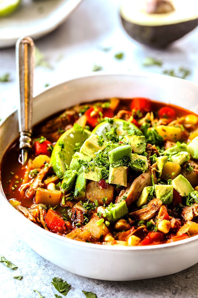 side view of a bowl of Caldo de Pollo Mexicano (Mexican Chicken Soup) with a spoon in the bowl topped with avocados