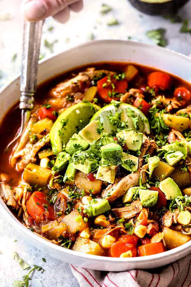 a hand holding a spoon in Caldo de Pollo (Mexican Chicken Soup) with poatoes, carrots, celery topped with avocados