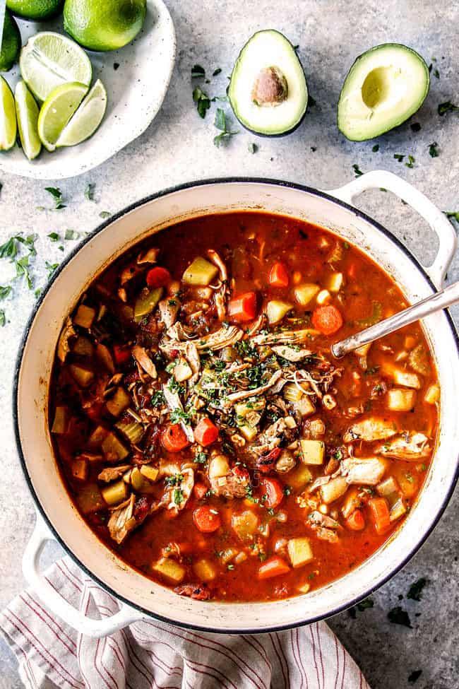 top view of a big white pot of Caldo de Pollo (Mexican Chicken Soup) with limes and avocados ready to garnish