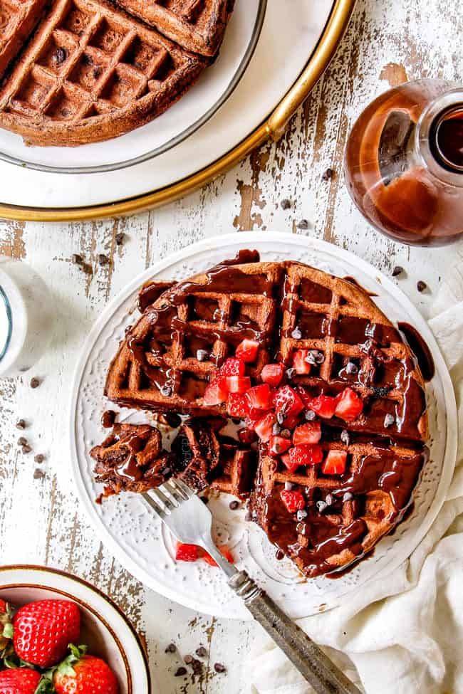 top view of healthy chocolate waffles with strawberries drizzled with chocolate