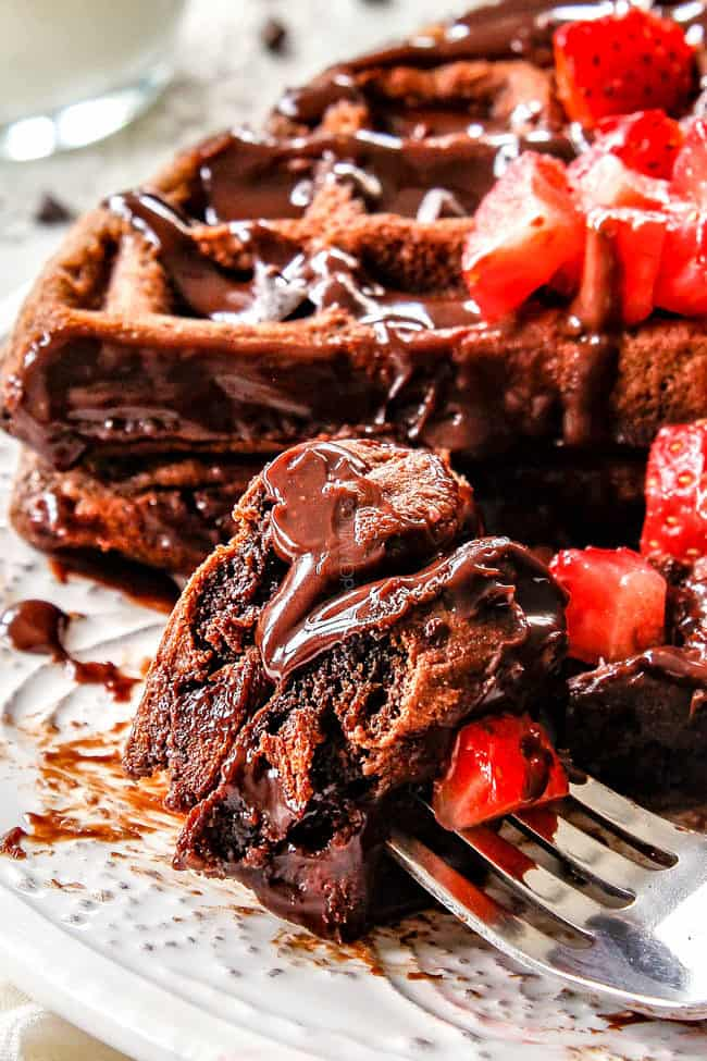 up close of double chocolate waffles on a fork with strawberries